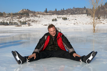 Man resting on ice after riding on skates