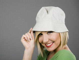 A blonde model in a silly white hat tipping it and smiling