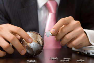 businessman playing a globe puzzle