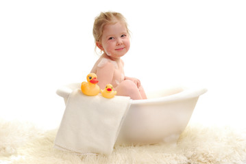 A young girl with bubbles in bathtub.