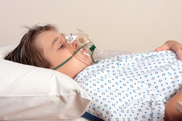 Child resting in bed has an oxygen mask or inhaler over face.