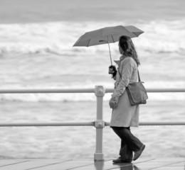 Chica bajo la lluvia paseando