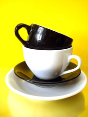 white and black cups on yellow background