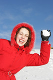 Young pretty woman playing snowball fight on flank of hill poster