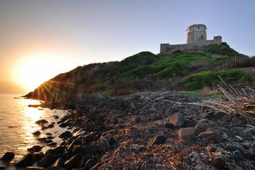 Ancient Sardinian castle on the coast during the sunrise