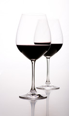 Zwei Weingläser halb voll vor weißem Hintergrund