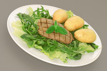 A plate of green leaf salad with baby potatoes and steak