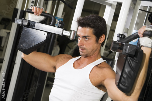 health club: guy in a gym doing weight lifting.