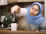 Muslim woman wearing a head scarf in a western kitchen  poster