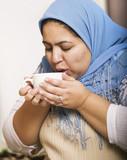 Muslim woman wearing a head scarf drinking coffee poster