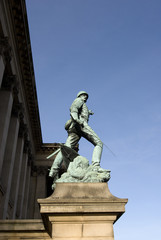 Copper statue of a soldier on a stone plinth