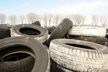 Heap of used car tires with trees in the background