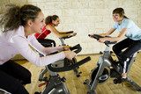 Fototapety Three happy, young women working out on exercise bicycle