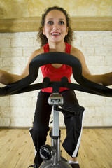 Young, happy woman working out on exercise bike at the gym