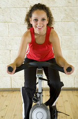 Young woman working out on exercise bike at the gym.