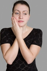Toothache. Beautiful woman on a grey background.