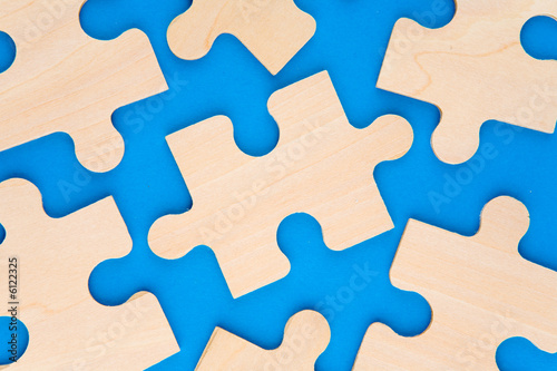 Wooden puzzle pieces on blue background