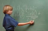 Nine year old boy doing advanced math on a chalkboard poster