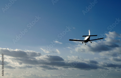 light aircraft on landing approach at sunset