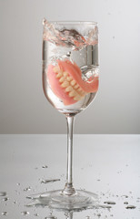 artificial Teeth splashing on wine glass
