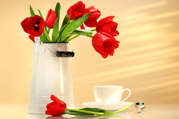Red tulips in white container with tea cup