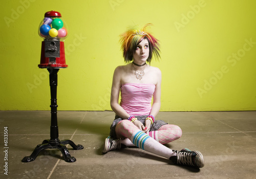 Colorful young punk girl sitting in front of a green wall