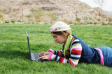 young girl is working on laptop at outdoor location