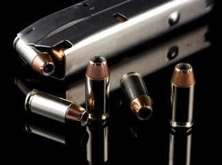 40 caliber bullets and clip on reflective black background