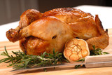 Fototapety Whole roasted chicken with garlic, rosemary and carving knife