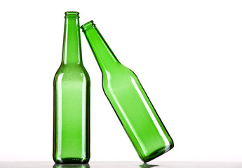 Green beer bottle falling on another one. White background.