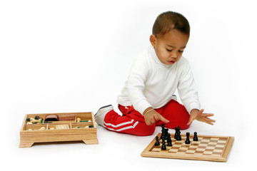 Little Toddler Putting  Chess Pieces on the Board