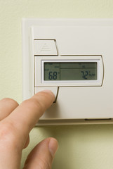 turning down a home thermostat to save energy