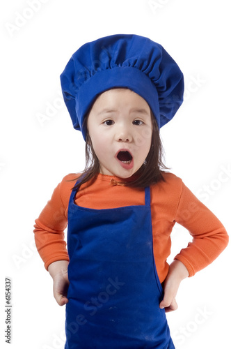 A young girl having fun in the kitchen making a mess