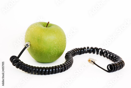 Green apple plugged with wire isolated on white