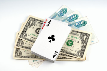 Banknote dollar and banknote rouble laid by fan and playing card