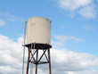 Water tower in farm against a cloudy blue sky