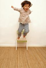 Kind springt vom Stuhl