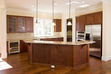 opulent kitchen with dark wood and stainless appliances poster