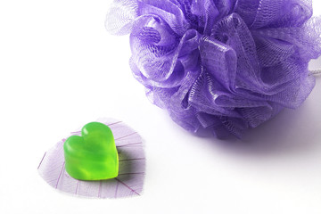 Violet bast whisp and a heart-shaped green soap on a dried leaf.