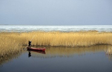 little boy in boat on partly frozen steppe lake in Kazakhstan