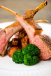 Roasted Rack of Lamb herb crusted on a white plate