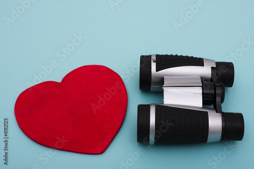 Heart shape with binoculars on blue background