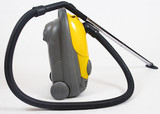 old yellow vacuum cleaner over white background poster