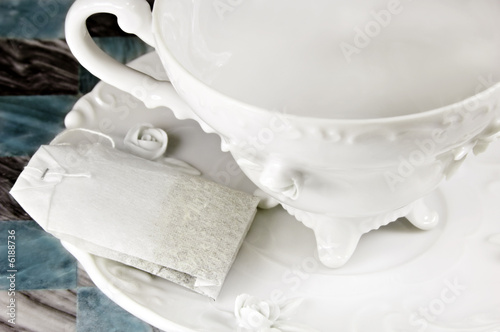 Tea bag and a white antique cup and saucer.