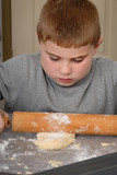 Child rolling dough poster