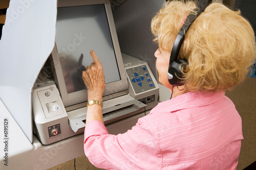 Senior lady using headphones for hearing impaired to vote