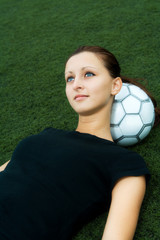 A beautiful soccer player resting on a soccer ball