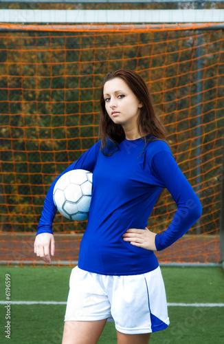 A beautiful soccer player carrying a soccer ball