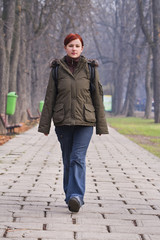 Image of a redheaded teenager walking in an autumn park.