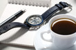 Watch and pen over notebook with cup of coffee near by